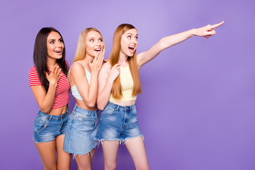 Advertisement concept. Portrait of surprised amazed girls in casual outfits watching away with unbelievable expression gesturing with forefinger isolated on vivid violet background
