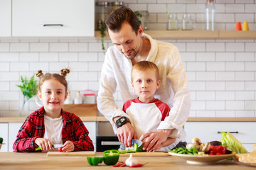 Image of father with daughter and son cooking at table