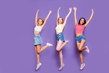 Portrait of cheerful positive trio with thin raised legs jumping in air holding arms up looking at camera isolated on bright violet background. Holiday vacation weekend concept