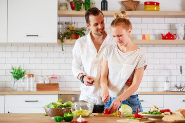 Picture of beautiful couple in love preparing breakfast in kitchen