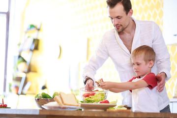 Image of man and son preparing salad