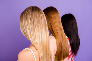Rear view portrait of trio with different hair color after haircut in beauty salon isolated on vivid violet background. Hair treatment therapy concept