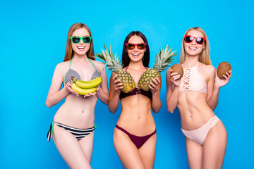 Wall Mural - Healthy nutrition food diet fitness fit lifestyle concept. Portrait of charming cheerful sisters with slender fir figure holding fresh fruits in hands isolated on bright blue background