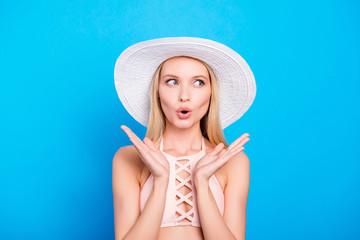 Wall Mural - Portrait of confused frustrated girl in head wear gesturing with hands looking to the side with eyes isolated on bright blue background. Pop grimace concept