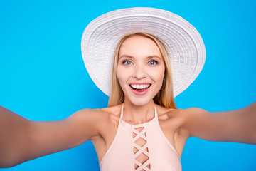 Self portrait of cheerful positive lady in pink outfit shooting selfie on front camera with two hands having online meeting isolated on bright blue background
