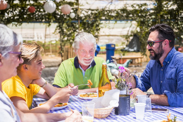 happy family eating together in outdoor restaurant. colors and happiness for cacuasian young and old people. son, father, grandfathers enjoy leisure activity in the nature