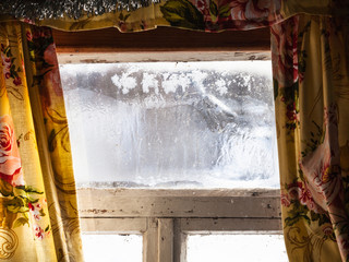 shabby frozen window in old russian rural house
