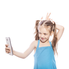 Young seven years old brunette girl in blue dress on a white isolated background. She makes selfie on her mobile phone, fun and smile emotions on her face