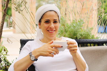 Outdoor portrait of 40 years old woman sitting in outdoor cafe