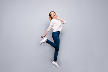 Portrait of trendy charming pretty funny comic blonde girl jumping in the air with raised leg posing looking at camera isolated on grey background, sport concept