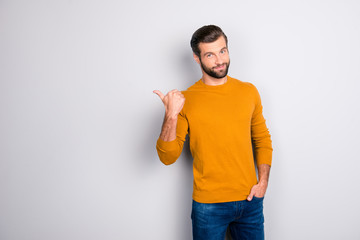 Portrait of cheerful attractive joyful confident guy keeping hand in pocket of jeans hinting pointing on copyspace behind his back isolated on gray background
