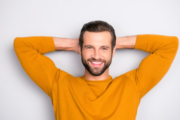 Close up portrait of cheerful excited joyful careless delightful dreamy handsome attractive guy dressed in yellow tight pullover having a rest isolated on gray background