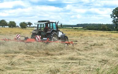Tracteur agricole qui retourne le foin en action sur le champ
