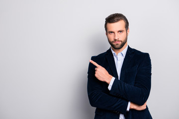 Portrait of handsome serious strict concentrated focused wealthy masculine virile elegant attractive banker with modern haircut pointing on empty blank space isolated on gray background copyspace Wall mural