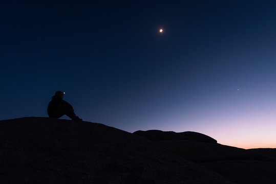 The silhouette of a lone hiker sitting on a rock formation in the desert with a headlamp shining under the moon and stars in a twilight sky with a fading glow to the west
