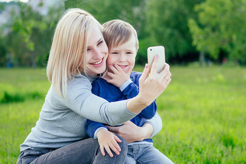 mother and her cute baby (son) make selfie on phone in the park on a background of green grass and trees