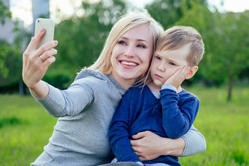 pretty blonde girl (mother) and cute son make selfie on phone in the park on a background of green grass and trees