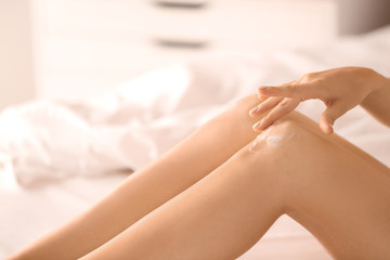 Young woman applying cream onto her leg after depilation, closeup