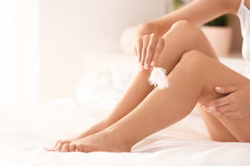 Young woman sitting on bed and showing silky skin after epilation