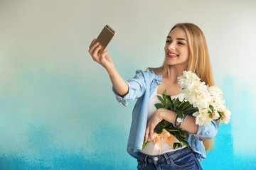 Attractive young woman with beautiful flowers taking selfie on color background