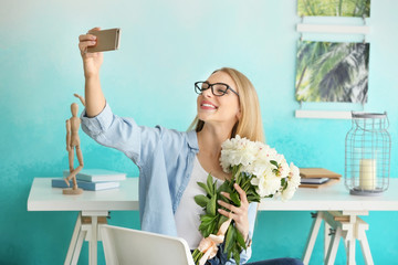 Attractive young woman with beautiful flowers taking selfie at home