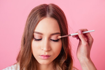 portrait of young and attractive girl and visagiste (makeup artist) applies makeup to the eye in studio on a pink background. concept of make-up skin care and beauty
