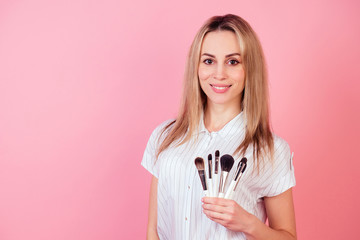 attractive blond visagiste make-up artist woman holding a makeup many brushes on a pink background in the studio. concept of cosmetology and skin care