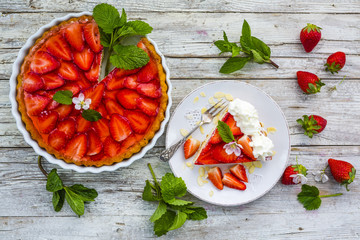 Delicious sponge cake with jelly and fresh strawberries on a wooden background.