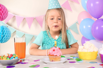 Little girl blowing out candle on birthday cupcake at home