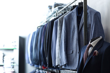 Racks with male clothes in boutique