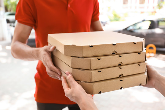 Young man giving pizza boxes to woman outdoors. Food delivery service