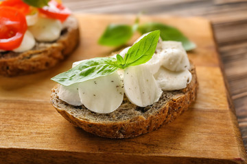 Tasty sandwich with mozzarella and basil on wooden board