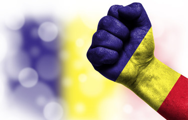 Flag of Romania painted on male fist, concept of conflict