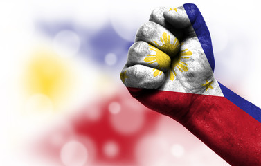 Flag of Philippines painted on male fist, concept of conflict