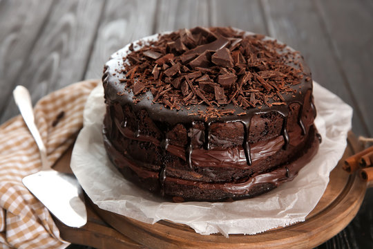 Board with delicious chocolate cake on wooden table