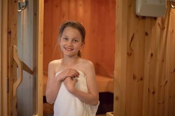 Ein Mädchen steht lächelnd vor dem Eingang der finnischen Sauna