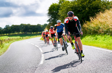 Cyclists racing on country roads on a sunny day in the UK. Wall mural
