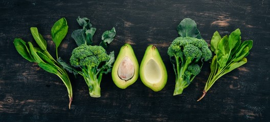 Fresh green vegetables and fruits on a wooden background. Healthy food. Top view. Copy space.