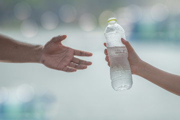 Hand sending or giving fresh, cold and clean drinking water, close up,