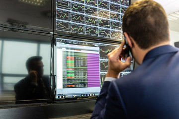 Businessman with cell phone trading stocks. Stock analyst looking at graphs, indexes and numbers on multiple computer screens. Stock trader evaluating economic data. Blue toned greyscale image.