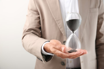 Businessman holding hourglass on light background, closeup. Time management concept