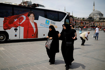 Two women make their way next to a bus with a picture of Iyi (Good) Party leader Meral Aksener in Eminonu district in Istanbul