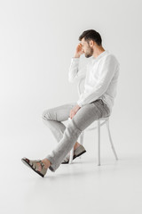 side view of thoughtful man in linen clothes sitting on chair  isolated on grey background