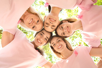 Beautiful women of different ages with pink ribbons outdoors. Breast cancer concept