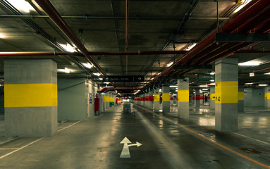Perspective view of empty indoor car parking lot at the mall. Underground concrete parking garage with open lamp at night. White direction sign. Choose way to live your life. Wiring and plumbing.