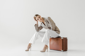 young stylish female model in linen jacket sitting on vintage suitcase and looking at camera isolated on grey background