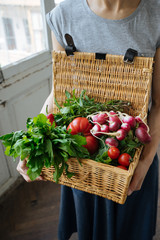 Female holding basket with vegetables and potherbs