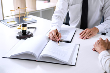 Businesspeople or lawyer having team meeting discussing agreement contract documents, judge gavel with Justice lawyers at law firm in background, Legal law, advice and justice concept