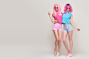 Wall Mural - Two Hipster Sisters Friends. Girls with Pink Fashion Hairstyle Having Fun Blowing lips. Young Beautiful Pretty Model Woman in Stylish Trendy Summer Outfit. Sweet colors