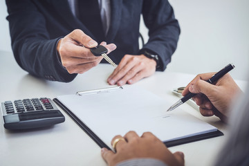 Salesman send key to customer after man signing car document contract good deal agreement, successful car loan contract buying or selling new vehicle